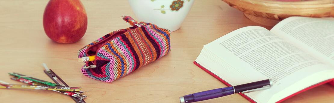 Buntes Federmäppchen aus Peru auf einem Schreibtisch mit Buch und Stiften