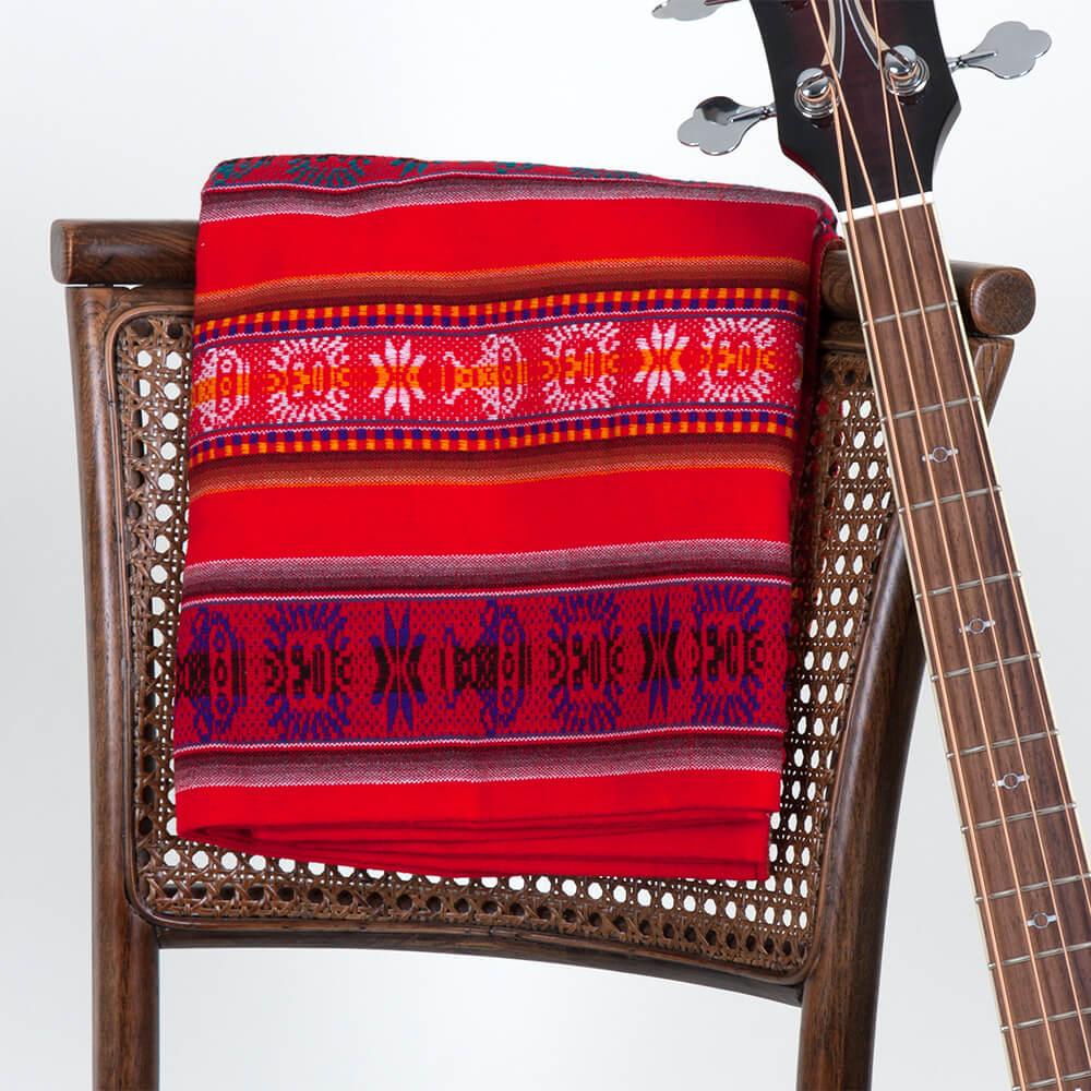 Aguayo Decke aus Bolivien, rot mit Symbolen über Holzstuhl, daneben steht eine Bassgitarre