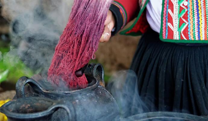 Wolle wird in einen Krug mit heisser Farbe getaucht - Färberin in Peru